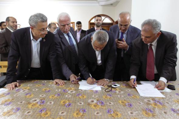 Head of the Hamas government Ismail Haniyeh and senior Fatah official Azzam Al-Ahmed sign a reconciliation agreement in Gaza City