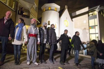 Muslims join hands to form a human shield as they stand outside a synagogue in Oslo