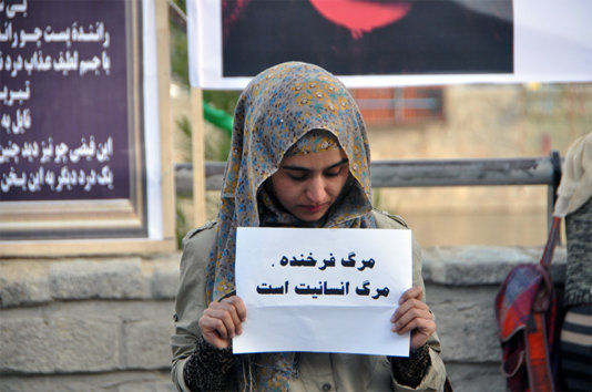 A girl carrying a card that says: \'The death of Farkhunda was the death of humanity\'.