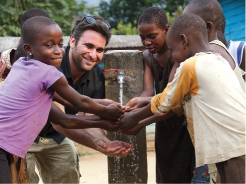 Josh Braunstein enjoys using first clean water (tap) with children in the village of Ekanjoh Bajoh.