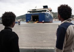 migrants wait to board a ferry