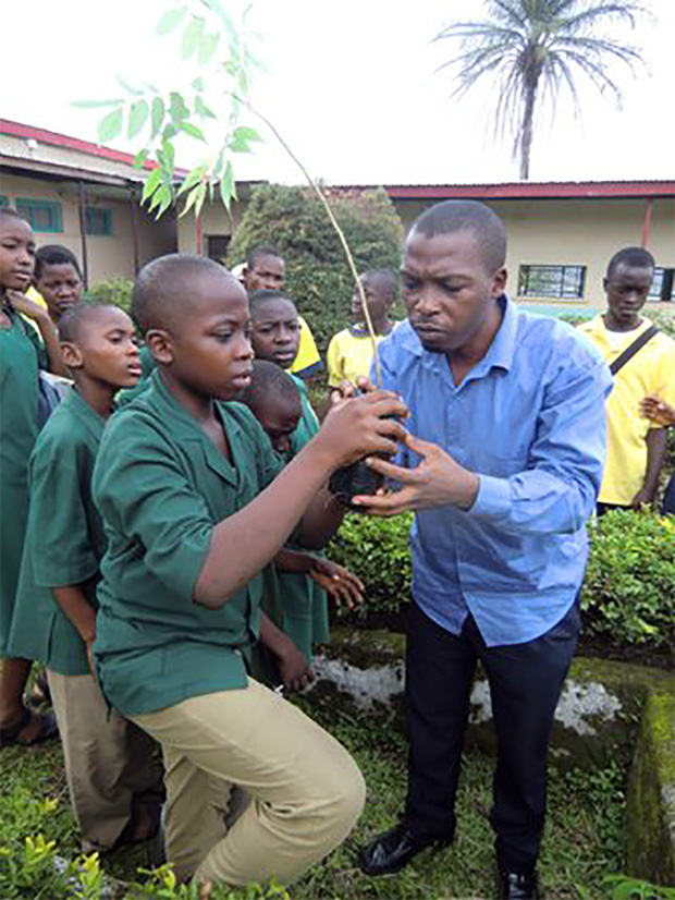 Green Cameroon\'s Executive Director Masango Sone handing trees to students for onward planting