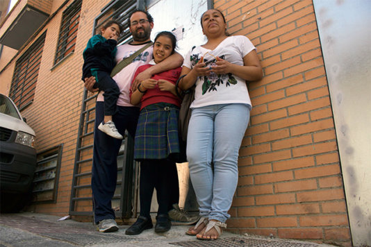 Lorena Meca's family in front of the squat building they were living in. Now it has been sealed by the bank.