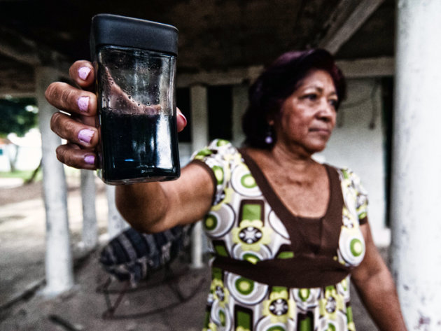 Elena Riquer, a Capoacán neighbour, shows the water she collected in a glass from the roof of her home after raining, blackend by the pet coke smoke.