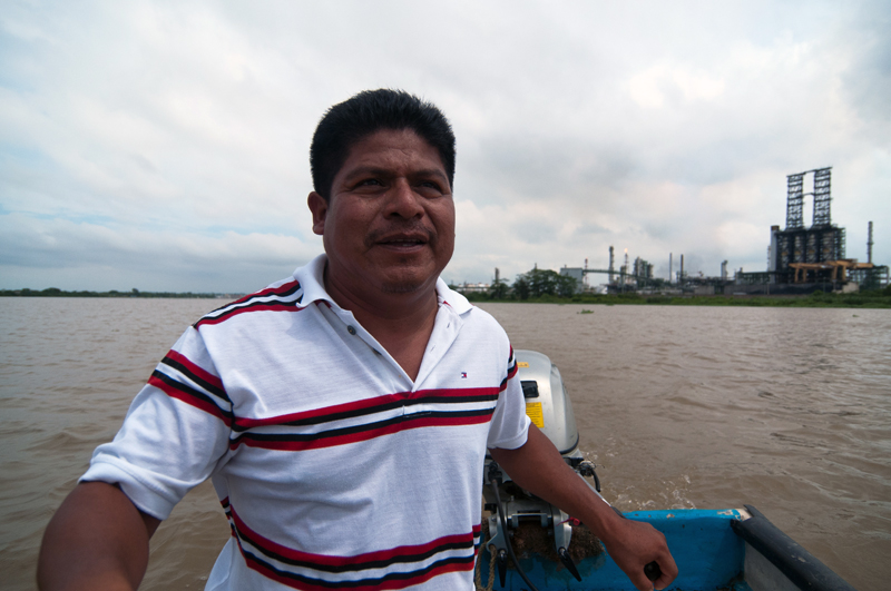 Juan Luis Francisco in a boat on the Coatzacoalcos river with the pet coke processing plant behind him.
