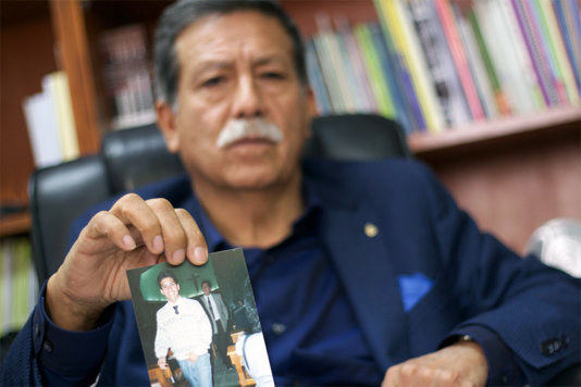 Julio César Jerí showing a photo of his disappeared son César Raphael Jerí.