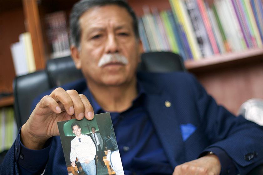 Julio César Jerí showing a photo of his disappeared son César Raphael Jerí.