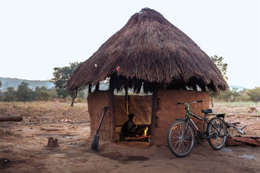 Tamara, a student in Zambia, cooks breakfast in the early dawn before she heads to school on her Buffalo Bicycle. Often girls must complete many hours of domestic chores before school.