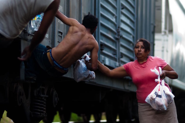 The Patronas handing the lunches to the migrants as the trains pass through La Patrona