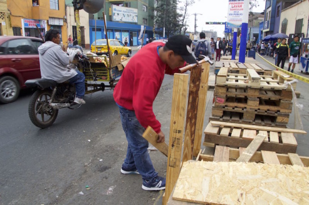 A volunteer prepares pallets to build a bus stop in a bustling avenue.