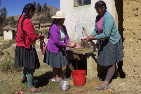 Women from Chocopía village washing cuy (an Andean guinea pig) before cooking it. Thanks to the 'water sowing' they have no more water problems.
