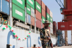 A soldier stands guard beside the Cosco Wellington, the first container ship to depart after the inauguration of the China Pakistan Economic Corridor port in Gwadar