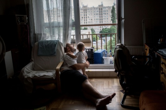 3rd District, Budapest, Hungary • Mónika Kovács, 32, Gábor Karácsonyi, 35, and Gergő Zalán Karácsonyi, 2.<br /> This young family lives in Óbuda, Békásmegyer, also known as Budapest's concrete jungle. Once the temperature starts to rise, the buildings become unbearably hot. In the morning, Moni takes Zalán (1.5 years) out to play in the park. When it is time to go back home for a nap, she keeps the lights out to avoid creating extra heat and using electricity. Once Gábor arrives home from work, they spend the evening together near the windows. It seems every waking hour is spent avoiding the sun and searching for a breeze.